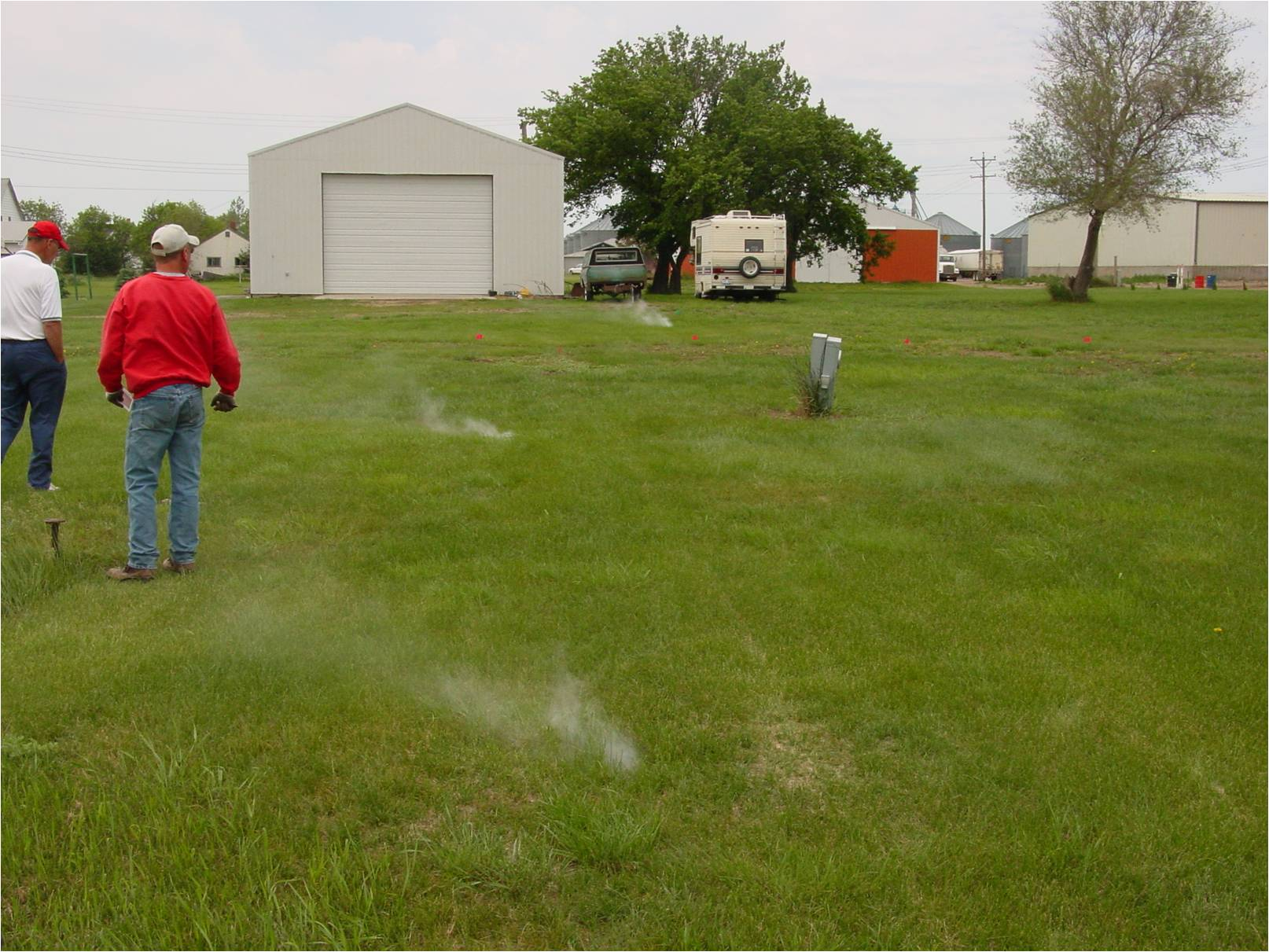 Smoke testing a sewer line with smoke rising out of the ground